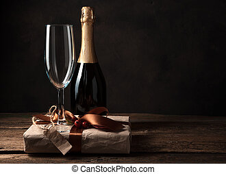 Gift box, champagne and wine glass on a dark wooden background.