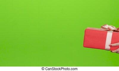 Gift box. Girl gives a man red box. Close up