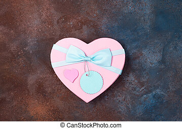 gift box heart with a ribbon on stone background, flat lay.