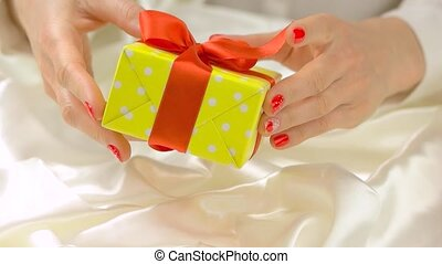 Gift box in delicate hands, slow motion. Well-groomed hands...