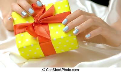 Gift box in female manicured hands. Young woman hands with...