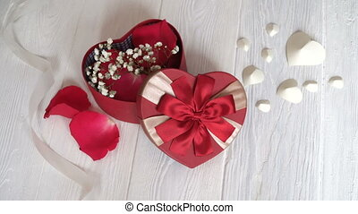 Gift box in form of heart and red ribbon on wooden white background. Top view