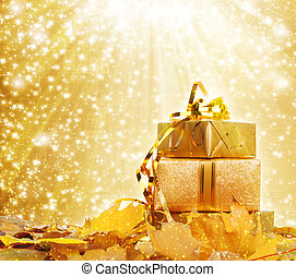 Gift box in gold wrapping paper with autumn leaves on the abstract glowing background
