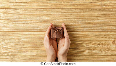 gift box in the hands on a wooden background