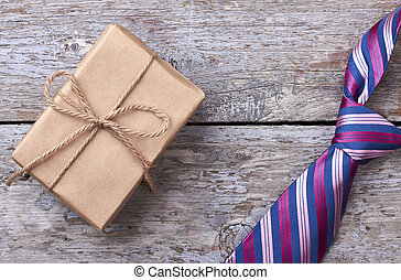 Gift box near striped necktie.