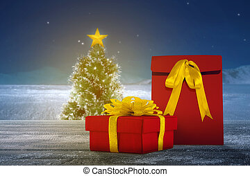 Gift box on a wooden table with a Christmas tree with a snowfall background