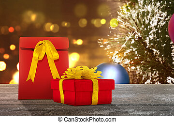 Gift box on a wooden table with a Christmas tree with blurred light background
