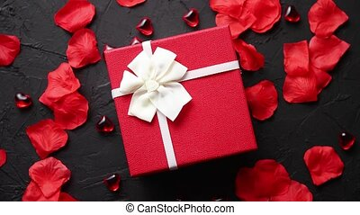 Gift box on black stone table. Romantic holiday background...