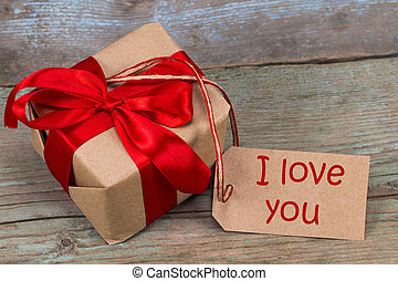 Gift box on the wooden background. Red ribbon. Valentine's Day gift