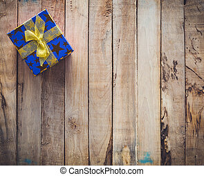 Gift box on wood background with space for text.