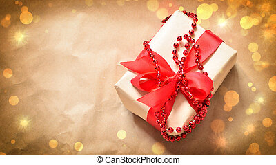Gift box tied red ribbon. Old wooden background.