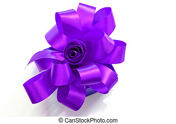 Gift box tied with a purple ribbon bow on white background.