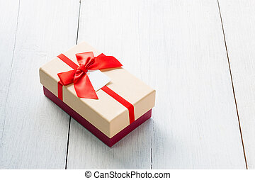 Gift box tied with red bow on white wooden background