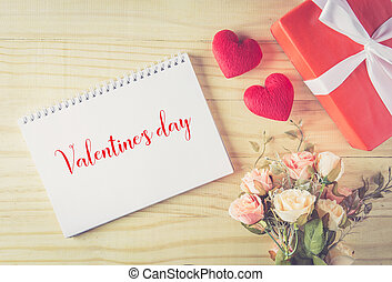Gift box white bow ribbon and heart valentine text with notebook on wood table background top view, february of valentine's day in concept.