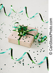 Gift box with a beautiful green bow on a light background with confetti stars