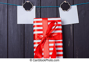 Gift box with a red bow on a wooden background