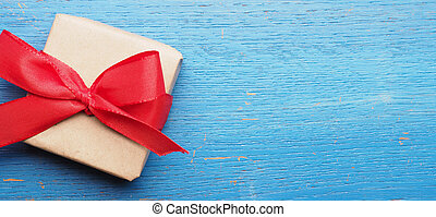 Gift box with a red bow on blue wood