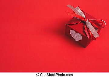 Gift box with a red bow on red background