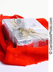 Gift box with a red ribbon on the red cloth, on a white background.