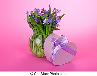 Gift box with a ribbon and flowers in vase