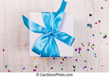gift box with blue bow on wood table