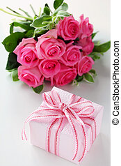 Gift box with bouquet of pink rose flowers on white background