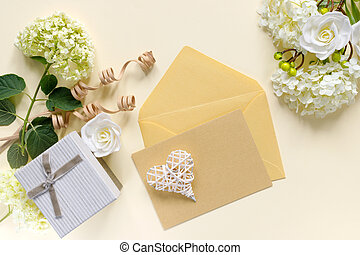 Gift box with bouquet of white hydrangea on beige table. Greeting card for the holiday. Envelope with invitation or congratulation.