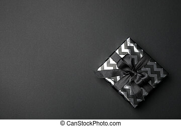 Gift box with bow on black background. Black Friday sale