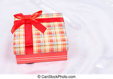 Gift box with bow over white satin