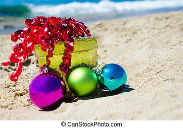 Gift box with christmas balls on the beach