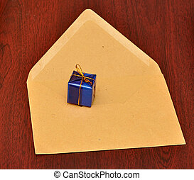 gift box with envelope on wood background