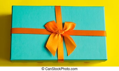Gift box with flower and little hearts moves and opens on yellow background top view stop motion
