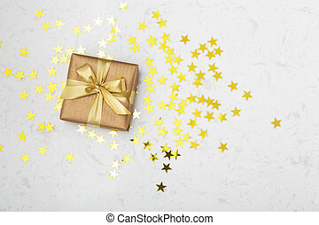 Gift box with gold star glitter on marble table background