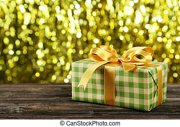 Gift box with golden bow on brown wooden background