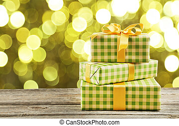 Gift box with golden bow on grey wooden background