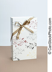 Gift box with golden ribbon bow on light brown and white background.