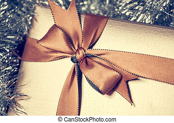 gift box with golden ribbon, glittery background