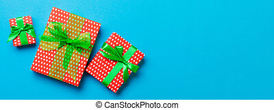 Gift box with green bow for Christmas or New Year day on blue background, top view