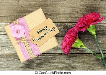 Gift box with Happy Mothers Day tag and carnations against rustic wood