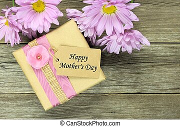 Gift box with Happy Mothers Day tag on rustic wood with purple daisies