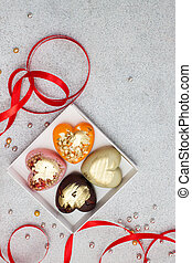 Gift box with heart shaped colored chocolate, decorated with red ribbon. Stone grey background.