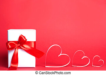 Gift box with hearts on red background. Top view, flat lay. St. Valentine's day greetind concept
