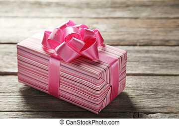 Gift box with pink bow on grey wooden background