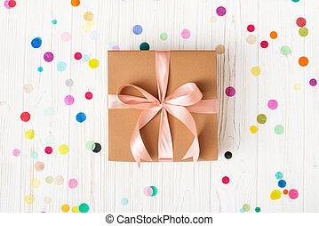 Gift box with pink ribbon on white background with multicolored confetti