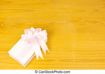Gift box with pink ribbon on wooden background.