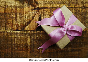 Gift box with pink ribbon on wooden background