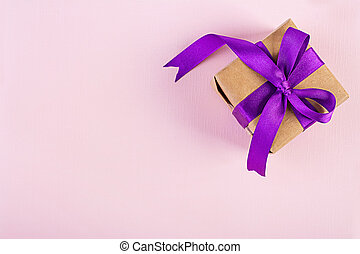 Gift box with purple ribbon isolated on pink background. Top view