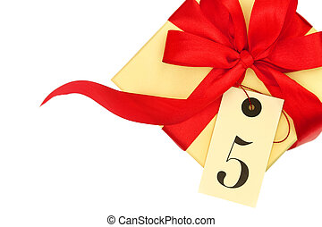 Gift box with red bow and tag with the number five isolated on white