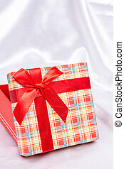 Gift box with red bow over white satin