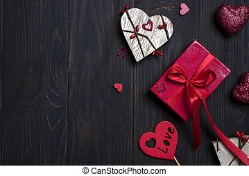 Gift box with red bow ribbon and wooden heart